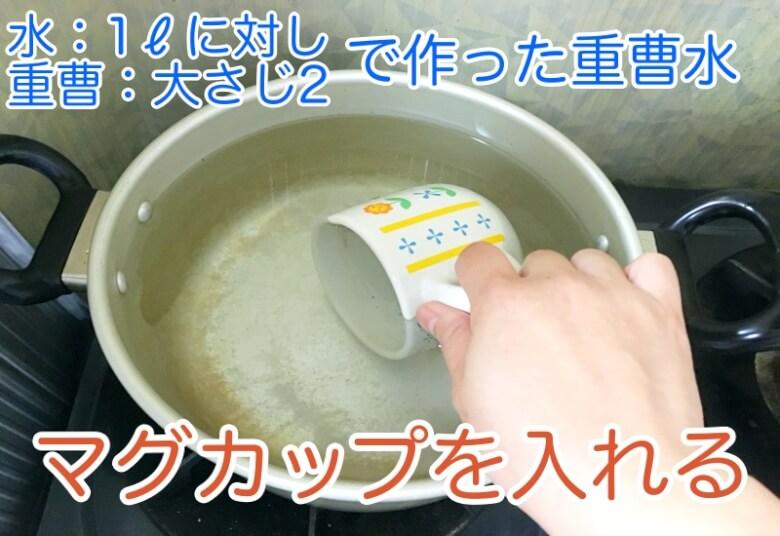鍋に重曹水を作りマグカップを入れる